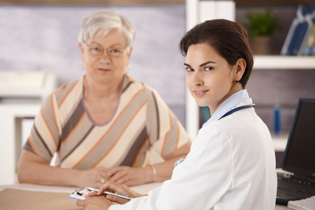 Portrait of female doctor talking to senior patient in office, looking at camera, smiling. Selective focus on doctor. Stock Photo - 8783436