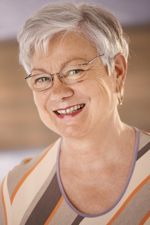 boomers: Closeup portrait of happy senior woman with glasses looking at camera, smiling.