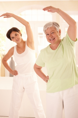Healthy elderly woman doing exercises with personal trainer at home, smiling. photo