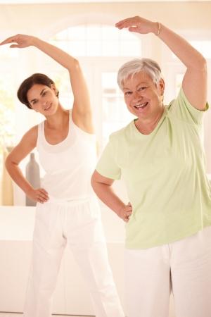 m�s viejo: Saludable anciana haciendo ejercicios con entrenador personal en casa, sonriendo.
