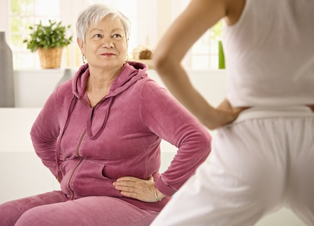 demonstrating: Elderly woman looking at personal trainer demonstrating exercise. Stock Photo