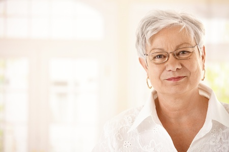 seniors homes: Closeup portrait of senior woman with glasses, looking at camera, smiling. Stock Photo