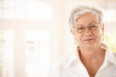 one senior adult woman: Closeup retrato de mujer senior con gafas, mirando a c�mara, sonriendo.