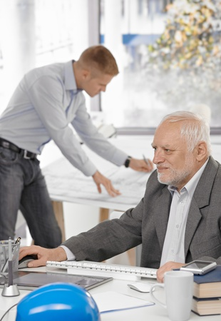 Senior businessman working on computer sitting at table, young architect standing at drawing board in background. photo