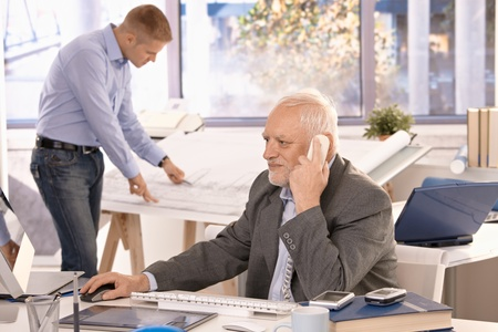 Senior businessman and young architect working in office, businessman talking on phone looking at computer screen, architect working on drawing table. Stock Photo - 8783631