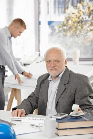 Portrait of senior architect in office, young designer working in background. photo