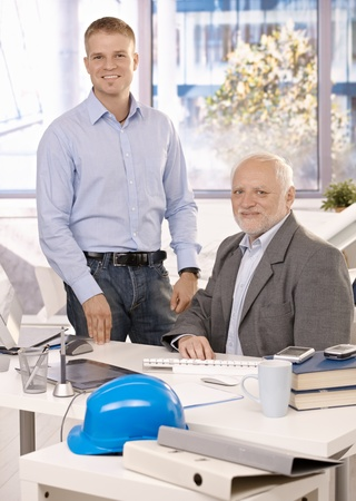 junior: Portrait of senior and junior businessmen working in office, looking at camera, smiling. Stock Photo