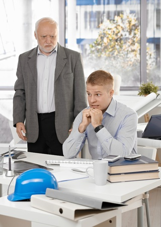 Scared young office worker man sitting at desk, angry senior executive standing. photo