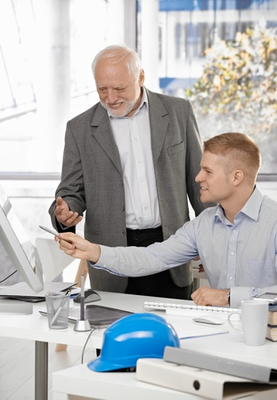Young architect discussing work on computer screen with smiling senior boss. photo