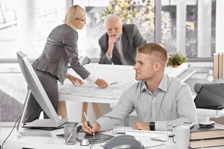 Designer team at work in office, young architect sitting at desk with drawing pad, older colleagues working on architectural plan. Stock Photo - 8783505