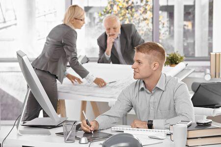 arquitecto: Dise�ador de equipo en el trabajo en la Oficina, el joven arquitecto sentado en el escritorio con dibujo pad, antiguos colegas trabajando en plan arquitect�nico.