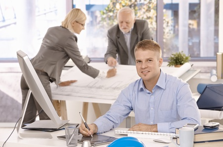 Young confident designer working on drawing pad, looking at camera, smiling, colleagues working in background. Stock Photo - 8783257