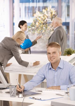 Young designer sitting at desk, colleagues working in background of bright office. Stock Photo - 8783433