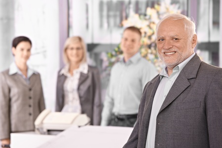 Portrait of senior executive businessman smiling at camera, with team standing in background. photo