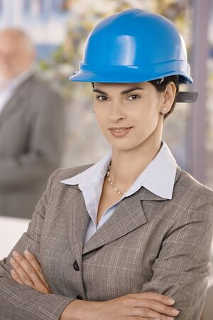 Portrait of businesswoman wearing hardhat, standing with arms crossed, smiling confidently at camera. Stock Photo - 8783773