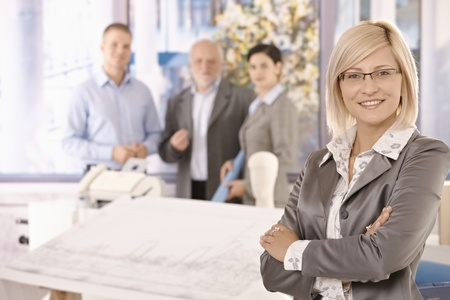 Confident businesswoman in focus smiling with arms crossed with team in background of office. photo