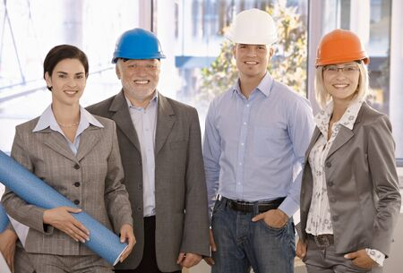 Happy designer team wearing hardhat in office holding architectural plan, smiling. photo