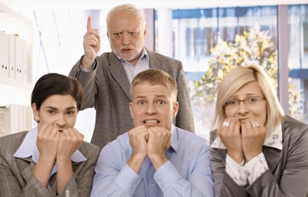 Angry boss shouting and pointing at scared employees in office. photo