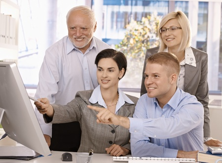 Smiling businessteam working together in office, looking at computer screen, pointing. Stock Photo - 8783625