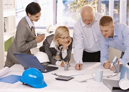 taking note: Allegro team di progettazione sul lavoro, architetto senior prendere appunti su Appunti, colleghi, guardando, sorridente. Archivio Fotografico