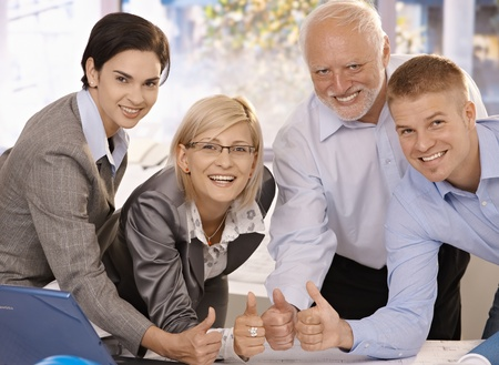 Successful businessteam standing together in bright office, giving thumbs up, smiling at camera. Stock Photo - 8783756