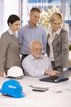 Senior architect showing work to businessteam on laptop computer, pointing at screen, smiling. photo