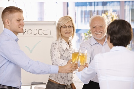 Smiling businessteam clinking champagne glasses, celebrating success in office. photo