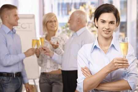 Smiling businesswoman holding glass of champagne, looking at camera, coworkers celebrating in background. Stock Photo - 8783434