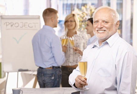 Portrait of senior businessman celebrating project done in office with champagne, employees talking in background. photo