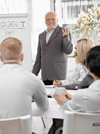 Senior businessman doing presentation to team, gesturing and smiling, standing at whiteboard. photo