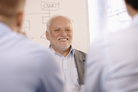 Portrait of senior businessman smiling, standing at whiteboard in office. photo