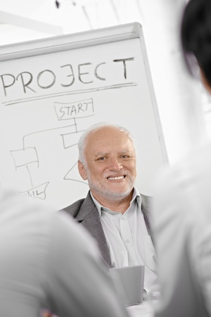 Smiling senior businessman presenting project at whiteboard, smiling. photo