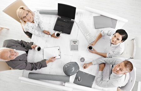 Portrait of business meeting, coworkers looking at camera from high angle view, smiling.