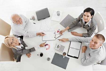 Smiling businesspeople sitting at meeting table, working, pointing at document, smiling at camera, high angle view. photo