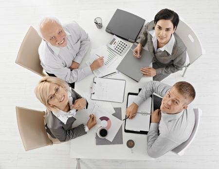 Smiling businesspeople at meeting, looking at camera in overhead view. photo