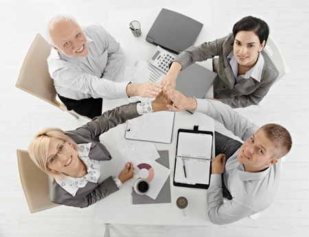 Businessteam raising hands together at meeting, expressing teamwork, sitting at table, smiling, overhead view. photo