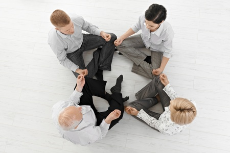 businessteam: Businessteam doing yoga meditation together in smart clothes, sitting on floor, overhead view. Stock Photo
