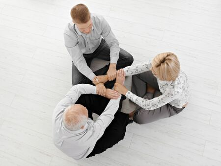 Three businesspeople meditating together, holding hands, expressing team spirit, sitting on floor, high angle view. photo