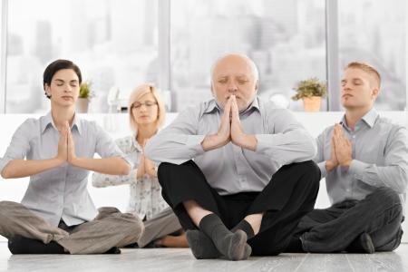 hombres haciendo ejercicio: Businessteam haciendo yoga Meditación vistiendo ropa formal, sentada en el suelo con los ojos cerrados en la Oficina. Foto de archivo