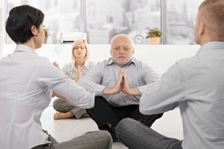 Businesspeople exercising yoga in office with eyes closed, focus on senior businessman. photo