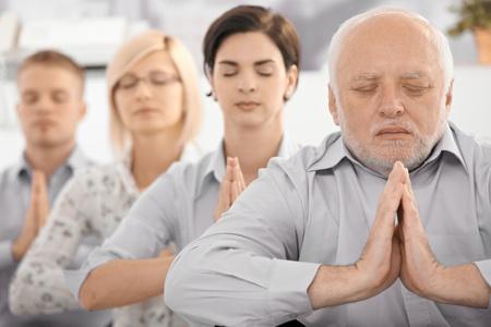 mujer meditando: Retrato de businessteam meditating, con el empresario senior en foco, ejercer con cerr� los ojos.