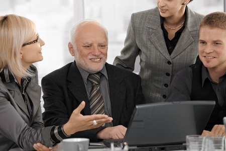 Businesswoman explaining work to colleagues, gesturing at laptop screen, smiling. photo