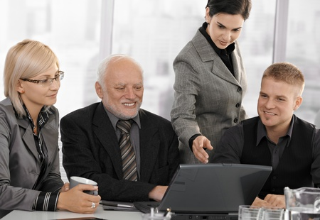 Businesspeople at meeting in office looking at laptop computer, businesswoman pointing at screen, smiling. photo