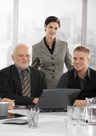 Portrait of confident businessteam at meeting table with laptop computer, smiling at camera. photo