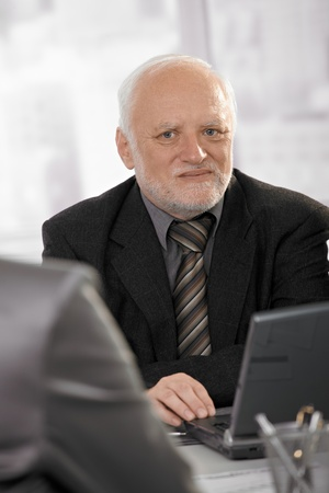 Portrait of senior professional looking at camera, using laptop computer at meeting. photo