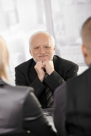 Portrait of confident senior businessman sitting on meeting, smiling. photo