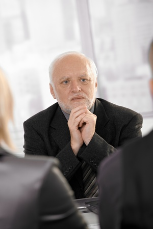 Experienced senior businessman concentrating, looking serious on meeting. photo