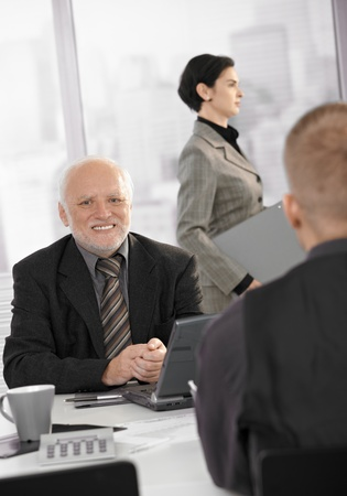 Senior businessman sitting at meeting table with young coworker, smiling, assistant in background. photo