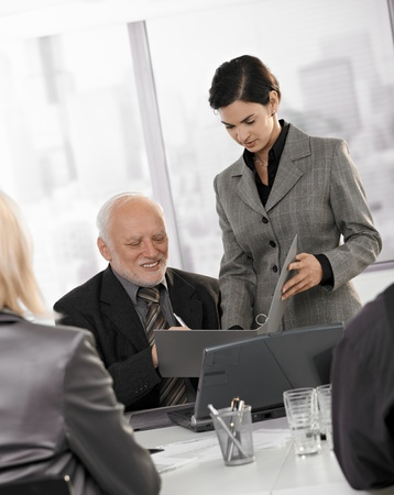 Mid-adult assistant holding documents to sign for senior executive at business meeting. Stock Photo - 8783621