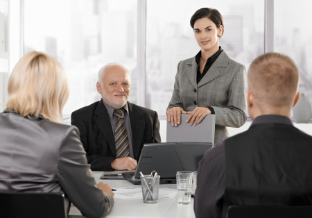 boardroom meeting: Businesspeople working at formal meeting together.